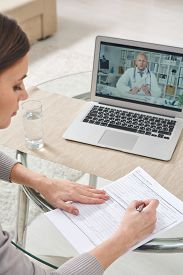 Over shoulder view of serious young woman filling papers and using laptop while talking to doctor via video link