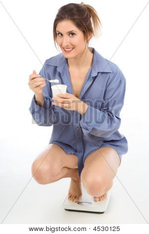 Woman On Weight Scales Eating Healthy Yogurt