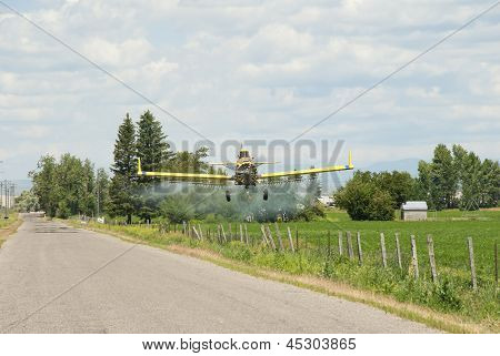 A spray plane flies over a farm and fenced fields on the High Desert of Idaho. poster