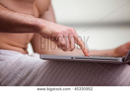 Mid section view of a man using a laptop