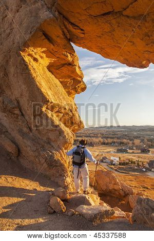 male hiker looking through a keyhole in Devil's Backbone Open Space at foothills of Rocky Mountains near Loveland, Colorado, warm sunset light