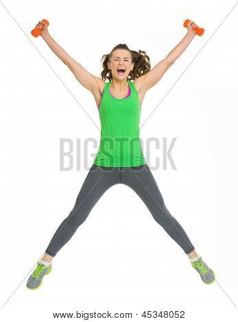 Happy healthy young woman with dumbbells jumping poster