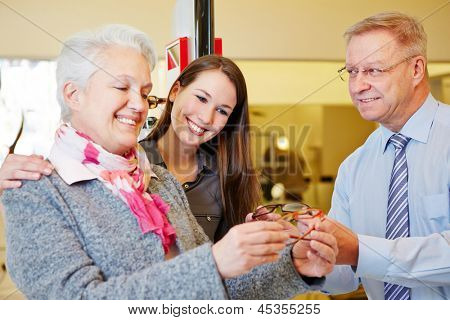 Elderly woman buying glasses with her grandchild at the optician
