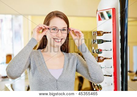 Young smiling woman with her new glasses at the optician