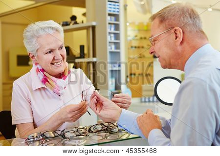 Elderly customer looking for new glasses at the optician