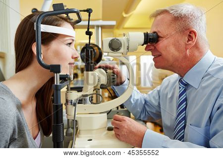 Ophthalmologist examing young woman with a slit lamp