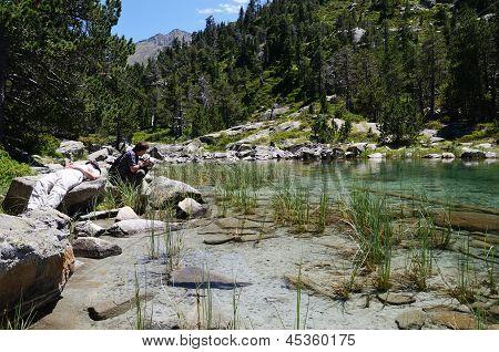 Tourists Near The Mountainous Lake