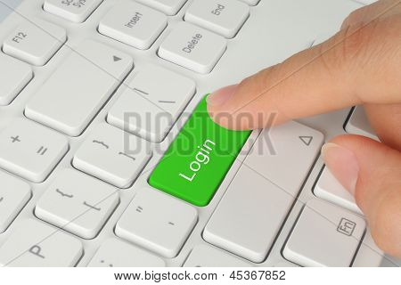 Hand pushing green login keyboard button