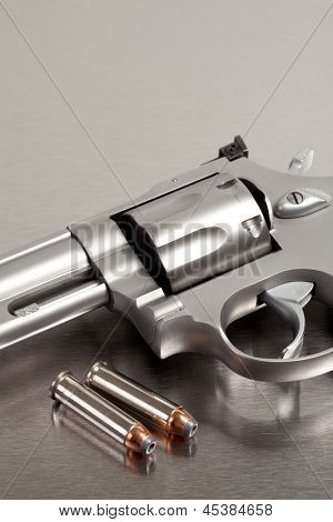 Handgun with bullets - modern revolver on brushed metal with two bullets