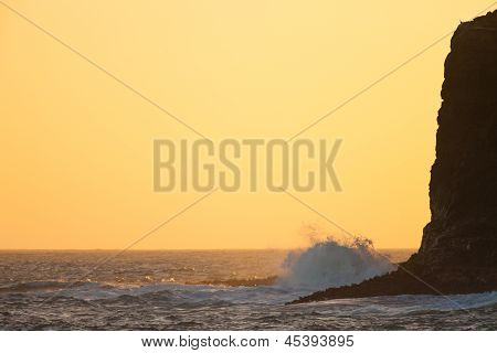 Sunset ocean scene wave pounds high cliff shore