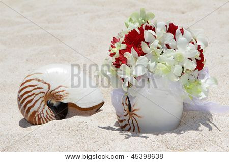 bridal bouquet with wedding rings in a shell on sand tropical beach