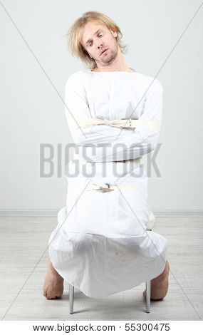 Mentally ill man in strait-jacket on gray background poster