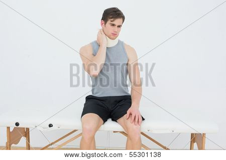 Handsome young man wearing cervical collar in the medical office