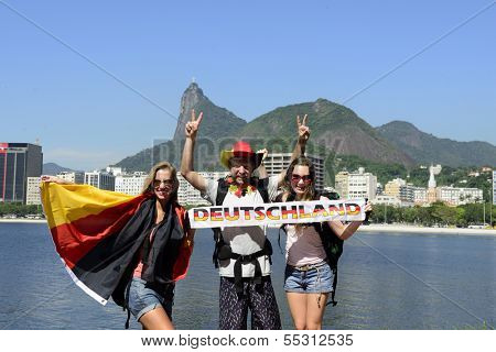 Group of sport fans friends traveling at Rio de Janeiro holding German flag, with Christ Redeemer in the background.
