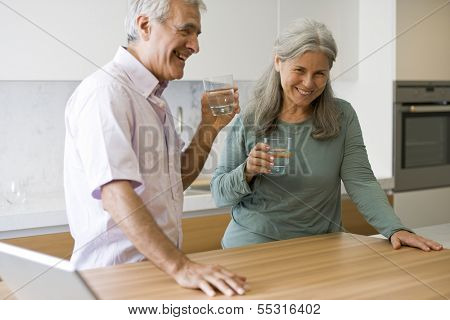 Senior couple drinking water in the kitchen