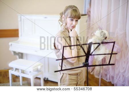 Beautiful girl stands near music stand in room with classic interior and piano.