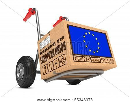 Cardboard Box with Flag of European Union and Made in European Union Slogan on Hand Truck White Background. Free Shipping Concept. poster