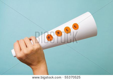 Hand holding free megaphone concept on blue background