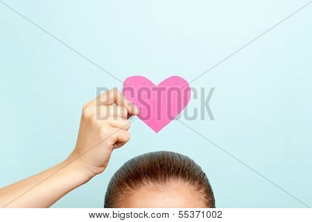 Happy Valentines Day Concept. A pink paper heart over head of a woman on blue background