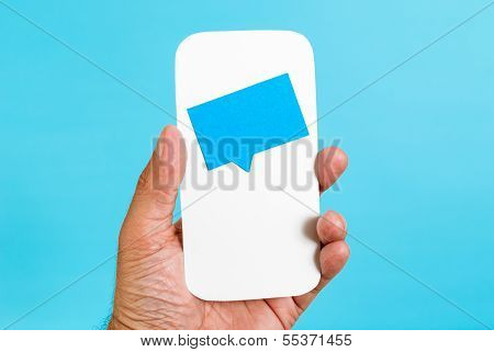 Mobile chat notifications concept on blue background. Hand holding a cellphone with a notification
