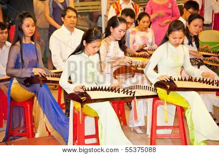 HO CHI MINH, VIETNAM- NOV 16, 2013: Unidentified Vietnamese musicians performing music on Zither, traditional instrument at the Labor Cultural Palace on Nov 16, 2013. in Saigon, Vietnam.