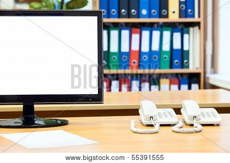 Isolated Clean Screen Of Lsd Monitor, With Two White Telephones On Office Desk