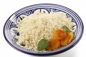 Plain couscous on a Tunisian handmade and hand-painted plate garnished with dried apricots and mint leaves poster