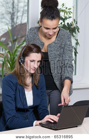 Two Women In Front Of A Notebook