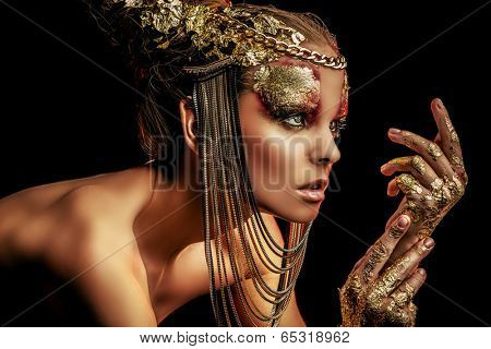 Art project: beautiful woman with golden make-up. Jewelry, make-up. Fashion. Over black background. poster