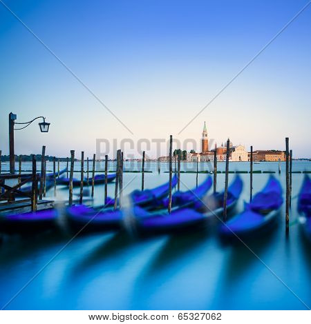 Venice, Gondolas Or Gondole On Sunset And Church On Background. Italy