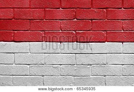 Flag of Monaco painted onto a grunge brick wall