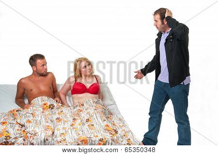 Surprised man finds his wife in bed with another man