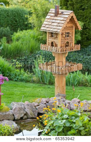 Homemade bird house next to a pond in the backyard