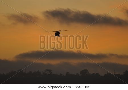 A USA Blackhawk helicopter silhouette at sunset. poster