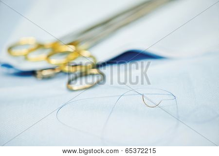 Surgery concept. suture needle and forceps. Shallow DOF.