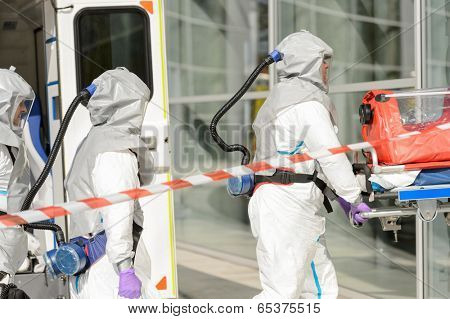 Hazardous material medical team with stretcher entering contaminated building