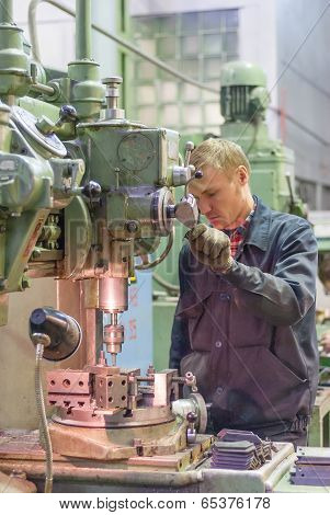 Worker drills bores on detail by driller