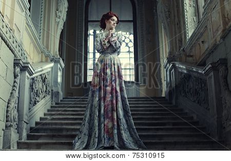 beautiful woman in elegant dress posing on stairs in old vintage interior