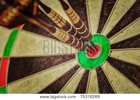 Vintage retro effect filtered hipster style image of - Success hitting target aim goal achievement concept background - three darts in bull's eye close up