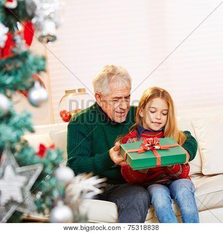 Granddad giving gift to granddaughter at christmas