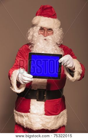 Santa Claus showing you a computer tablet pad, on studion background.