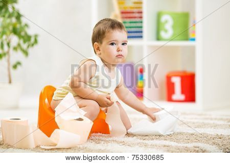 kid boy sitting on chamber pot with toilet paper