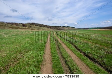 The Dirt Road Between The Field And The Slope