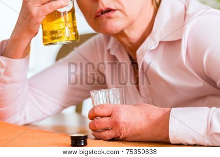 Old woman with alcohol problem sitting at home drinking hard liquor