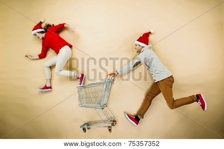 Christmas couple with trolley on beige background