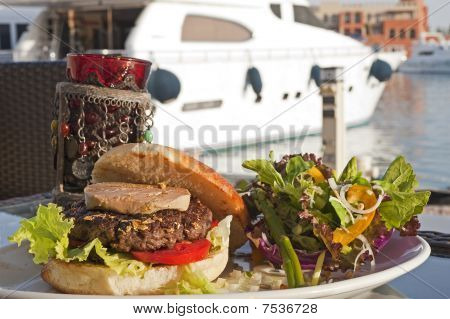 A gourmet burger with fois gras and gold leaf in a private marina next to a motor yacht poster