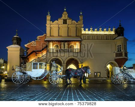 Horse carriage parked in front of Gothic Cloth Hall Sukiennice on the Main Market Square in Krakow by night poster