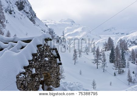 Mountain hut made of stones at winter in Slovenian Alps