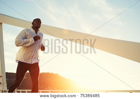 Male runner in windbreaker jogging over bridge road at sunset poster