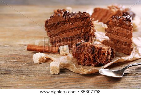 Slices of tasty chocolate cake on plate on table close up
